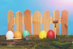 Oeufs colorés peints de Pâques à la barrière en bois sur la mousse verte Images stock