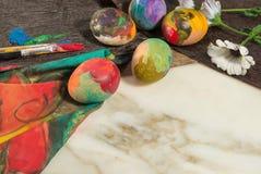 Oeufs colorés de Pâques avec des fleurs de ressort et deux brosses du peintre Photos stock