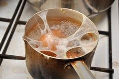 Oeufs criqués bouillant dans la casserole Photo libre de droits