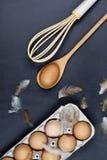 Oeufs, cuillère en bois, favori et plumes images stock