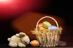Oeufs décorés des fils et des perles lumineux de couleur dans le panier Photos stock
