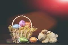Oeufs décorés des fils et des perles lumineux de couleur dans le panier Image libre de droits