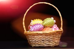 Oeufs décorés des fils et des perles lumineux de couleur dans le panier Images libres de droits