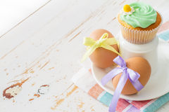 Oeufs décorés du ruban et des petits gâteaux sur le fond en bois blanc Photographie stock