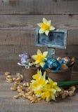 Oeufs décoratifs de Pâques en pot et fleurs des narcisses Photographie stock
