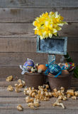 Oeufs décoratifs de Pâques en pot et fleurs des narcisses Image libre de droits