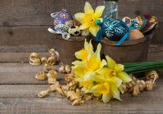 Oeufs décoratifs de Pâques en pot et fleurs des narcisses Photo stock