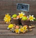 Oeufs décoratifs de Pâques en pot et fleurs des narcisses Images stock
