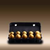 Oeufs d'or dans un carton noir Photo stock
