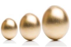 Oeufs d'or de d'isolement sur un fond blanc Photographie stock