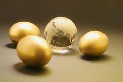 Oeufs d'or et globe en cristal Photo stock