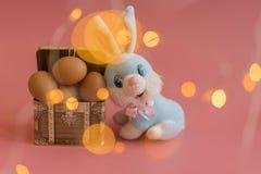 oeufs dans un coffre et un lapin de Pâques Concept de Pâques sur le fond rose Bokeh photo stock