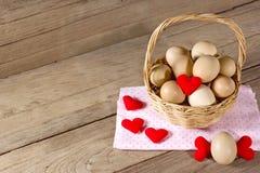 Oeufs dans un panier en osier avec en forme de coeur sur la table en bois Photo libre de droits