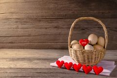 Oeufs dans un panier en osier avec en forme de coeur sur la table en bois Photos stock