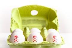 Oeufs dans un paquet de Livre vert avec les oeufs peints avec un crâne toxique rouge et des os de symbole de risque photographie stock libre de droits