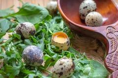 Oeufs de caille crus frais dans la cuill?re en bois avec des feuilles de salade d'arugula et d'?pinards sur la paille rustique et photo stock