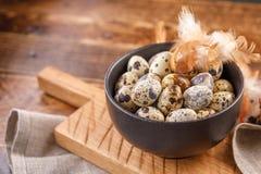 Oeufs de caille dans la tasse en céramique, serviette, panneau en bois sur la table en bois Oeufs de caille semblables en couleur Images libres de droits