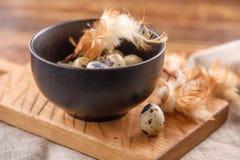 Oeufs de caille dans la tasse en céramique, serviette, panneau en bois sur la table en bois Oeufs de caille semblables en couleur Images stock