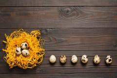 Oeufs de caille dans le nid décoratif et un certain nombre d'oeufs de caille sur le fond en bois foncé La vue à partir du dessus  Photographie stock libre de droits