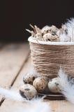 Oeufs de caille dans le pot de Pâques sur une table en bois Image stock