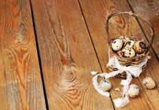 Oeufs de caille dans un panier sur une table en bois Photos libres de droits