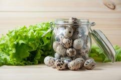 Oeufs de caille dans un pot en verre et des feuilles de laitue image libre de droits