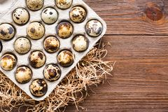Oeufs de caille dans une boîte et une paille sur une table en bois Photo stock