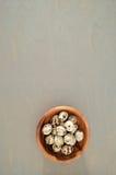 Oeufs de caille dans une cuvette en bois sur un fond gris Photo stock
