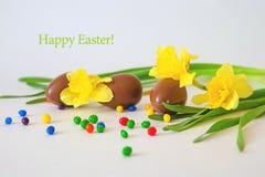 Oeufs de chocolat de Pâques et jonquilles fraîches de ressort sur le fond blanc superficiel par les agents l'espace de copie - Jo Photo libre de droits