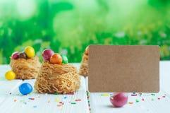 Oeufs de chocolat peints dans les nids doux avec la carte vide image stock