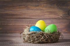 Oeufs de couleur de Pâques dans le nid sur le bois photographie stock