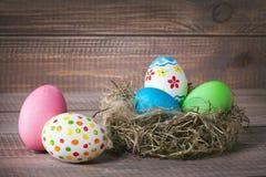 Oeufs de couleur de Pâques dans le nid sur le bois images stock