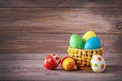 Oeufs de couleur de Pâques dans le panier sur le bois Images stock