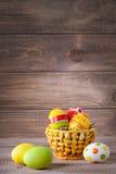 Oeufs de couleur de Pâques dans le panier sur le bois image stock