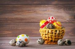 Oeufs de couleur de Pâques dans le panier sur le bois photographie stock libre de droits