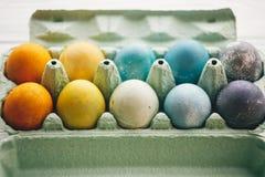 Oeufs de pâques élégants dans le plateau de carton sur le fond en bois blanc Oeufs de pâques colorés modernes peints avec le colo image stock