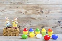 Oeufs de pâques avec des coquetiers et des lapins Image stock