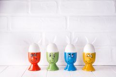 Oeufs de pâques avec des oreilles de lièvres dans les supports Photo libre de droits
