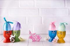 Oeufs de pâques avec des oreilles de lièvres dans les supports Photographie stock libre de droits