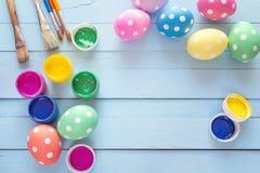 Oeufs de pâques avec des pots de peinture et de brosses sur un fond bleu image libre de droits