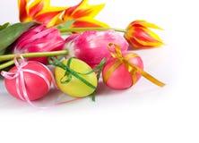 Oeufs de pâques avec des proues et des tulipes Image stock