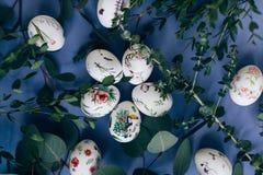Oeufs de pâques avec l'ornement floral sur la table bleue photos libres de droits