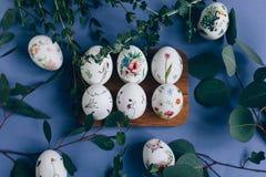 Oeufs de pâques avec l'ornement floral sur la table bleue images stock