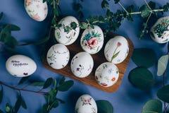 Oeufs de pâques avec l'ornement floral sur la table bleue photo stock