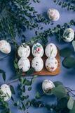 Oeufs de pâques avec l'ornement floral sur la table bleue photographie stock