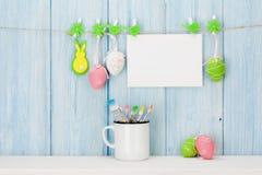 Oeufs de pâques, carte de voeux et pinceaux colorés Photos libres de droits