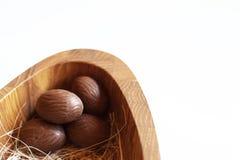 Oeufs de pâques de chocolat dans le plat en bois sur le fond blanc Image libre de droits