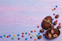 Oeufs de pâques de chocolat et bonbons colorés sur un fond en bois de lavande avec l'espace de copie, vue supérieure Concept de P photos stock