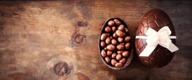 Oeufs de pâques de chocolat sur le fond en bois foncé avec le ribbo de couleur photographie stock libre de droits