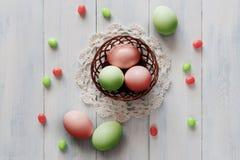 Oeufs de pâques colorés avec des sucreries dans le petit panier Photos stock